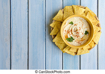 Hummus and corn chips, on blue wood table - Healthy homemade...