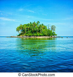 An atoll in the sea surrounded by blue sky and water with...