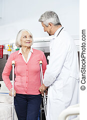 Senior Patient Being Assisted By Doctor With Crutches -...