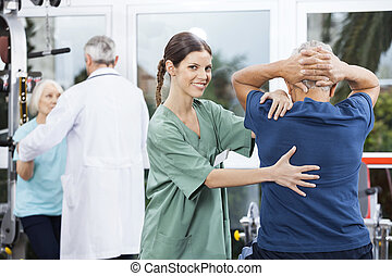Female Nurse Assisting Senior Man In Back Exercise -...