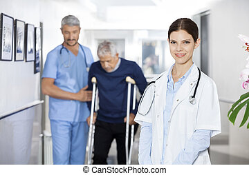 Doctor Smiling While Colleague Assisting Senior Man With...