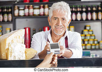 Senior Man Accepting Payment From Customer In Cheese Shop