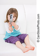 little girl with mobile phone on sofa