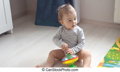 Cute little baby playing with colorful toys at home