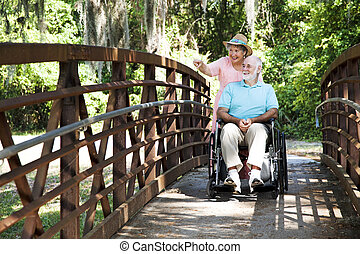 Disabled Seniors in Park - Senior woman pushing her disabled...