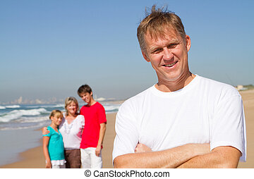 father with family in background
