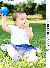 sweet baby girl - a sweet baby girl in park holding blue...