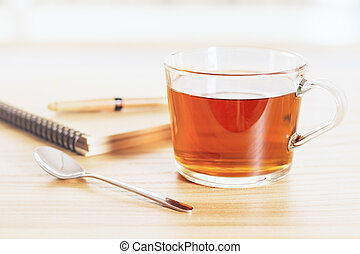 Tea and copybook - Cup of tea on wooden table with teaspoon...