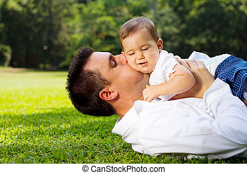 loving father with baby girl - a loving father kissing his...