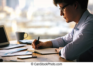 Businessman writing in copybook - Sideview of businessman...