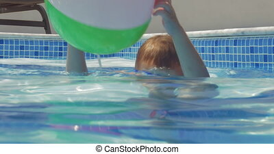 Little playful child with ball in pool
