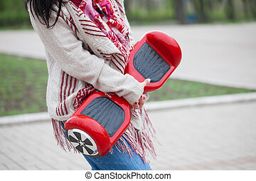 electric mini segway hovev board - Womanl holding modern red...