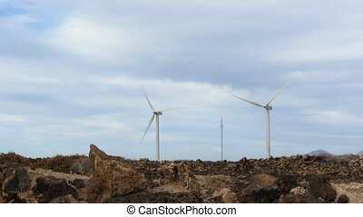 Two Wind Generators on Rocky Ground with Stones and Bright...