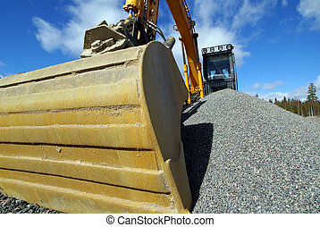 Hydraulic excavator at work. Shovel bucket against blue sky...