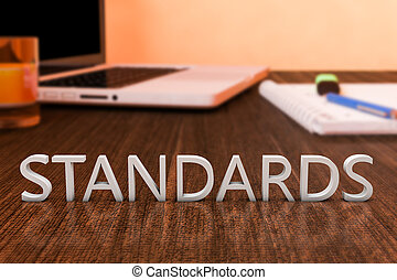 Standards - letters on wooden desk with laptop computer and...
