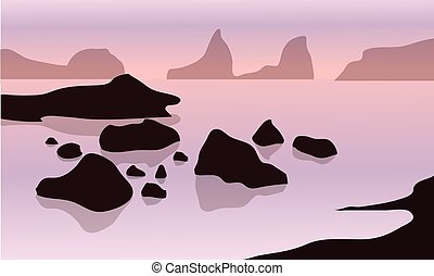 Silhouette of rock in beach with pink backgrounds