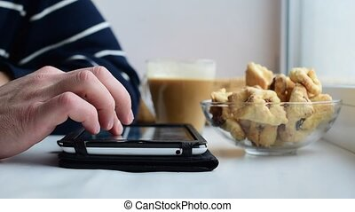 Hands of caucasian man using tablet on window sill - Hands...