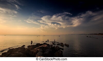 Silhouettes in Shallow Sea Rocks on Beach at Sunset - view...