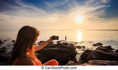 Camera Moves from Girl with Iphone to Seascape at Sunset -...