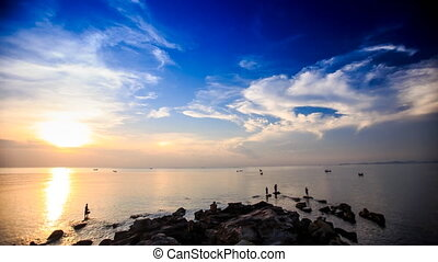 Silhouettes in Sea by Rocks Boats Sun from Behind Clouds -...