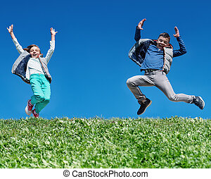 Happy children jumping on meadow