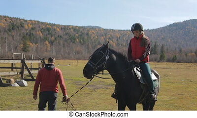 The equitation trainer is leading the horse on a leash with the female jockey sitting in the saddle.