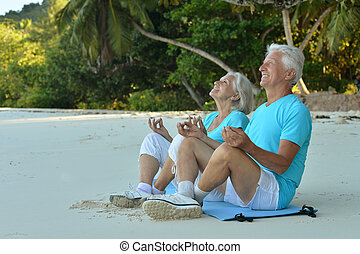 elderly couple meditate on beach - Happy elderly couple...