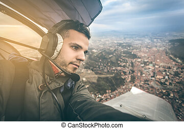 young pilot flying an ultra light model above the city, - a...