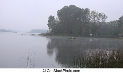 fisherman in misty early morning on lake at country region...