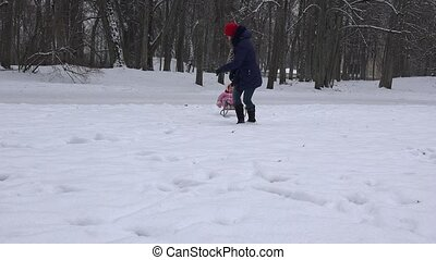 Caucasian woman pulling baby child on sled through snowdrifts. 4K