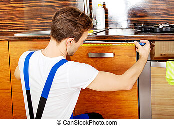 Young repair man measuring kitchen cabinet