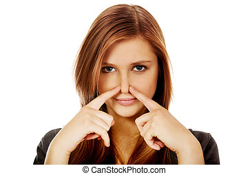 Young woman pinches nose with fingers hands looks.