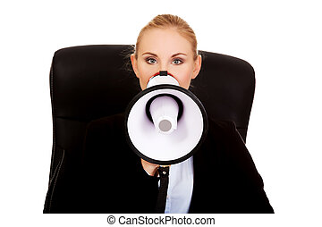 Business woman sitting on armchair and screaming through a...