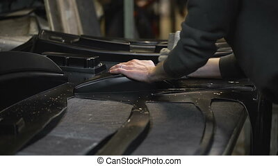 Worker carves plastic parts from a sheet Details obtained by...