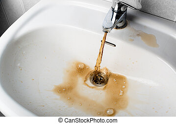 Dirty brown water running into a sink - Dirty brown water...