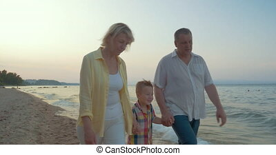 Grandparents and little grandchild walking on the beach -...