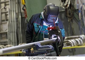 Industrial worker setting orbital welding machine -...
