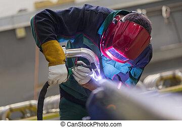 Industrial worker welding in metal factory - Industrial...