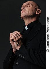 sacerdote, posición, con, ojos, cerrado, y, praying,...