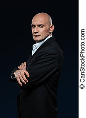 Mature businessman standing with arms folded on dark...