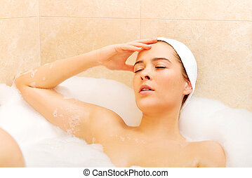 Young woman relaxing in bath.