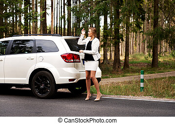 Young woman with broken car in the middle of forest.