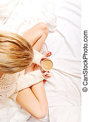 Young woman sitting in bed with a cup of coffee