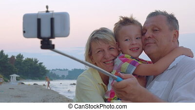 Family mobile selfie with child and grandparents - Cheerful...