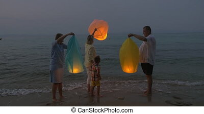 Family flying sky lantern on the beach - Family with mother,...