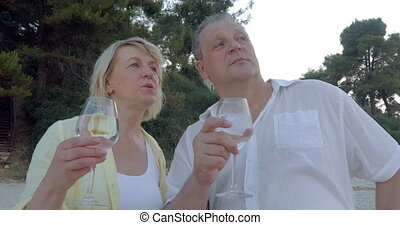 Man and Woman Having Drink and Talk Outdoor - Mature man and...