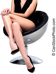 Woman with long legs sitting in a chair, isolated on white...