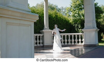 Bride and groom dance outdoor in sunny day. They whirl in a...