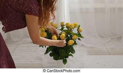 Woman put roses to the vase - Young woman put yellow roses...