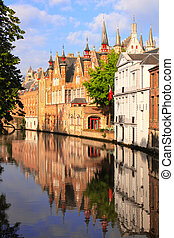 Medieval buildings along a canal in Bruges, Belgium -...